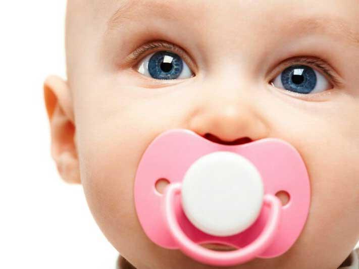 مکیدن پستانک صورتی توسط نوزادی زیبا