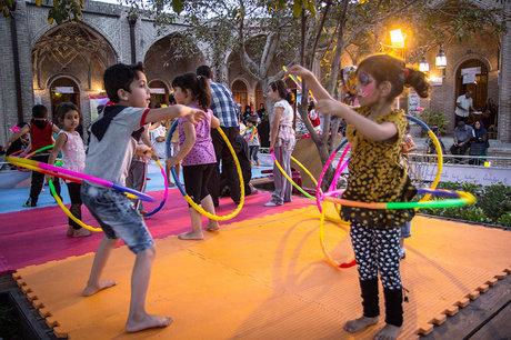 یکی دیگر از راه های افزایش خلاقیت در کودکان بازی است. بچه ها در حیاط مشغول بازی با حلقه های رنگی هستند.