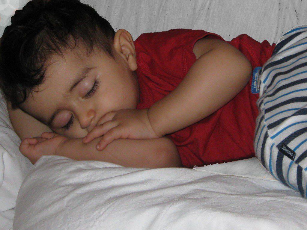 مکیدن انگشت توسط پسر دو ساله ای در تخت بخواب رفته است.