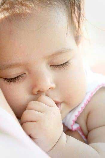 دختر یکساله ای که در آغوش والدین به خواب رفته است.
