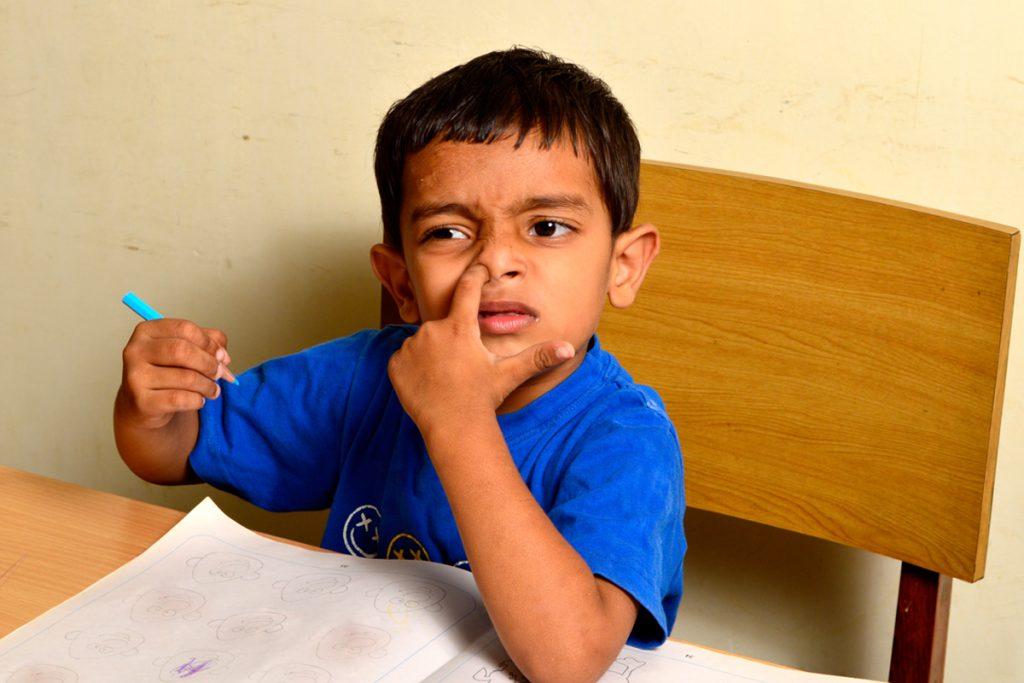 پسری که در کلاس درس دست در بینی کرده است.